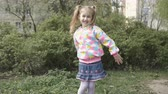 The child is actively playing and moving fun. Little schoolgirl dances outdoors and rejoices. Happy 7 year old girl dancing on the street