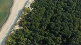 bałtyk : Video from above, aerial view of a beautiful Wild Island. Aerial view. 4K UHD. Flying on a drone in wild along coast. Epic view. Aerial top view of summer green trees in forest. Seascape at sea coast