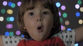 Boy Looks Surprised and Happy to Receive Surprise. Portrait Little Boy Opening Eyes and Looking at Camera. Christmas New Year Background. Child Looks Into Camera With Delight and Surprise at Face. Стоковые видеозаписи