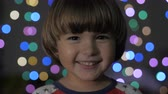 Cute Little Boy With Standing Against Glowing Christmas Lights Smiling at Camera. Portrait Child Looking at Camera. Christmas New Year Background. Lovely Boy Posing On Christmas Lights Background Стоковые видеозаписи