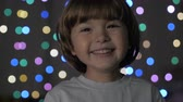oslava : Cute Little Boy With Standing Against Glowing Christmas Lights Smiling at Camera. Portrait Child Looking at Camera. Christmas New Year Background. Lovely Boy Posing On Christmas Lights Background Dostupné videozáznamy