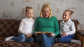 Mother reads two daughters a book Стоковые видеозаписи