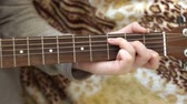 Womens fingers on the strings of the guitar