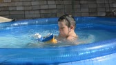 play video game : Boy is playing with the toy ship in the pool. Stock Footage