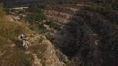 camiseta : A young man on a moto bike rides along the cliff of the canyon. Aerial view 4k Vídeos