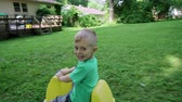 nevetés : the little boy playing in the playground slides down from a hill 4k Stock mozgókép