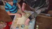 sister : Grandmother teaches her grandson and granddaughter how to cook cookies in a small kitchen. The woman helps the children to cut figurines out of the dough, shooting above the table. Stock Footage