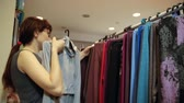 sem fio : A young woman in a gray blouse and glasses makes a choice of a new sweatshirt from colorful clothes hanging on her shoulders on a hanger in a ready-made clothing store. Vídeos