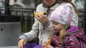 tart : Mother and daughter eating sandwiches sitting on a bench in a cold overcast afternoon. Young family at lunch outdoors. A brunette woman and a little girl are dressed in warm outerwear.