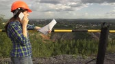 есть : A young female worker in an orange helmet stand on a hill before fence over open pit , holds a document in her hand, then speaks on the phone. Стоковые видеозаписи