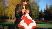 crocheting : A young brunette woman in a black leather jacket crochets knit a red and white plaid in the shape of a star, sitting in an autumn or winter park. A girl makes a gift by hand for Christmas.