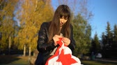 crochet : A young brunette woman in a black leather jacket crochets knit a red and white plaid in the shape of a star, sitting in an autumn or winter park. A girl makes a gift by hand.