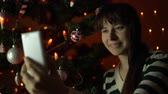 cardigan sweater : A young woman in a striped sweater takes a selfie on a white smartphone on the background of a Christmas tree at the end of the evening.
