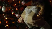 cardigan sweater : A young woman opens a gift box, the brunette sits under a Christmas tree on a background of yellow lights in the early morning or at night indoors.