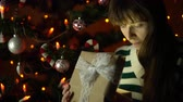 cardigan sweater : A young woman opens a gift box, the brunette sits under a Christmas tree on a background of yellow lights in the early morning or at night indoors, close-up. Stock Footage