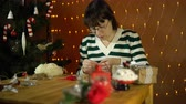 skein : A young brunette woman in a striped sweater is making ornaments in the form of a Christmas candy cane in the room on a background of yellow electric lights.