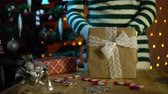 yellow dog : A young woman in a striped sweater puts a soft toy dog in a beige gift box, standing next to a decorated Christmas tree on a background of yellow electric lights. Stock Footage