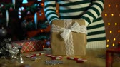 cana : A young woman in a striped sweater puts a soft toy dog in a beige gift box, standing next to a decorated Christmas tree on a background of yellow electric lights. Stock Footage