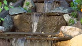 rocks nger : Close-up of the artificial waterfall in the park, clear water runs along the stone steps, slow motion.