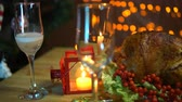 christmas dish : In the glass pour champagne next to the fried bird on a plate with a salad on the table on a background of yellow electric lights with a festive Christmas dinner in the evenings. Stock Footage