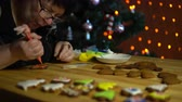 glaze : A mature woman decorates with icing homemade ginger cookie sitting at a wooden table next to a decorated Christmas tree in the evening on the eve of the holiday. Stock Footage