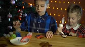 buzlu yüz : Children cover with multicolored glaze gingerbreads, next to the Christmas tree on the background of electric yellow lights on the eve of the holiday in the evening. Stok Video