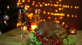 hálaadás : A roasted bird on a platter with a salad next to a glass of champagne stands on a table amidst yellow electric lights with a festive dinner in the evenings. Stock mozgókép