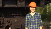 полдень : A young woman worker in orange helmet stands near a mining excavator, looks in the camera and smiles.