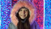 beautification : Portrait of a happy woman in a gray warm jacket next to a sparkling glowing dangling multicolored lights on the street in the evening.