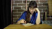 aveia : A young, sleepy woman with glasses unwillingly intends to eat oatmeal, a brunette sitting at a wooden table next to a brick wall.