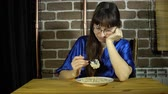 kukoricapehely : A young, sleepy woman with glasses unwillingly intends to eat oatmeal, a brunette sitting at a wooden table next to a brick wall.