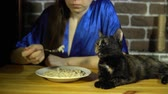 aveia : A young woman in a blue robe eats oatmeal, next to a plate a dark cat sits on a light wooden table.