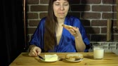 köntös : A happy young woman in a blue smock spreads butter on a slice of multigrain bread, then bites off a piece and smiles looking into the camera, the brunette sits next to a brick wall, 4K.