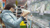 glass dishes : A young woman in a warm jacket chooses white plates in the department of crockery in a supermarket.