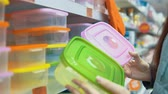 comprador : A young woman chooses a plastic food container in the department with utensils in the supermarket.