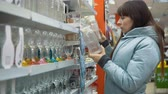 glass jugs : A young woman chooses a glass jug in the department with utensils in the supermarket. Stock Footage