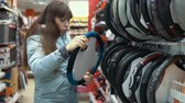 úsek : A young woman chooses a case for steering the car in the department of accessories and spare parts for autos.