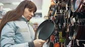 non stick : Customer womans selects a pan with non-stick coating in the tableware section of the hypermarket.