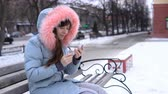 queda de neve : A young woman in a warm warm jacket talking on the phone and sitting on a bench outside in the winter.