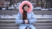 bonde : Portrait of a young happy woman in a gray coat sitting on a bench outside on a winter day.