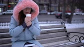 toka : A young woman in a gray warm jacket drinking a cup of coffee, a brunette sitting on a bench outside in the winter. Stok Video