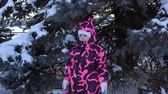 Portrait of a happy child in a pink overalls next to a blue fir in the woods on a winter day. Wideo