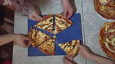 The top view of the hand takes a pizza cut from a plate on the table. Adults and children at the same time stretch their hands to get pieces of pizza.