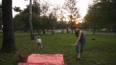 Mom and daughter playing together on the grass in the park on a summer evening at sunset Wideo