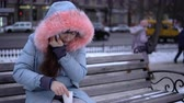 congelação : A young woman in a gray warm jacket talking on the phone and drinking hot tea or coffee from a paper cup, a brunette sitting on a bench outside in the winter. Stock Footage
