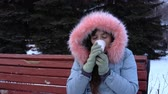 congelação : An frozen girl in a gray warm coat drinking hot tea or coffee from a paper cup, tries to warm herself sitting on a bench in a city park next to fir-trees on a snowy cold winter day. Stock Footage