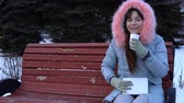 congelação : A young woman in a gray warm jacket drinking hot tea or coffee from a paper cup, a brunette while sitting on a bench in a city park next to fir-trees on a snowy winter day.