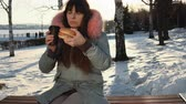cena urbana : A young freelancer woman in a gray warm park sits on a bench eating a burger in a city park in winter at sunset.
