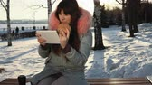 dziennikarz : A young woman blogger in a gray warm parka sits on a bench, uses a digital tablet and drinking hot tea or coffee from a paper cup, in a city park on a snowy winter day.