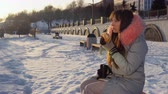 блог : Portrait of a young woman eating a burger and enjoying the application in a smartphone to create content for her blog, sitting on a bench in winter during sunset.